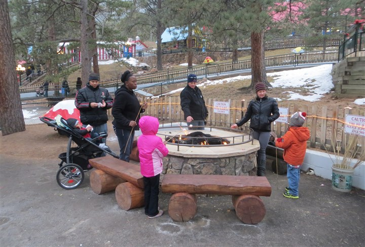 Visitors to North Pole Visitors to North Pole: Home of Santa's Workshop roast marshmallows over an open fire.