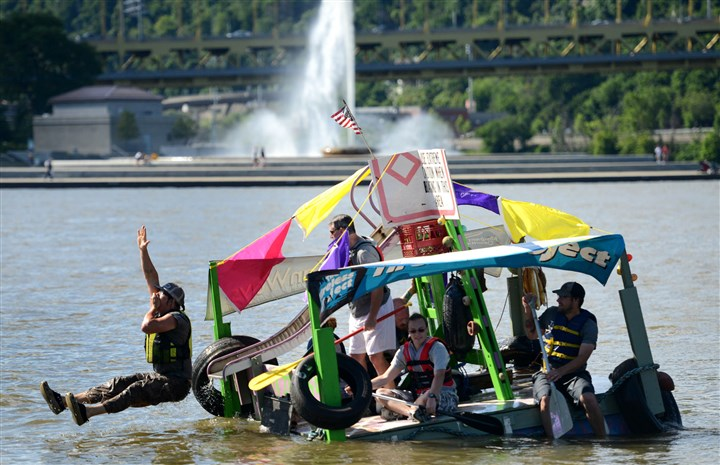 Evan Clark of Polish Hill slides into the water  Evan Clark of Polish Hill slides into the water Friday off a boat constructed by The Tireless Project during the Anything That Floats race on the Allegheny and Ohio Rivers in Downtown Pittsburgh. The Tireless Project created the boat solely from objects they have pulled out of Pittsburgh rivers.