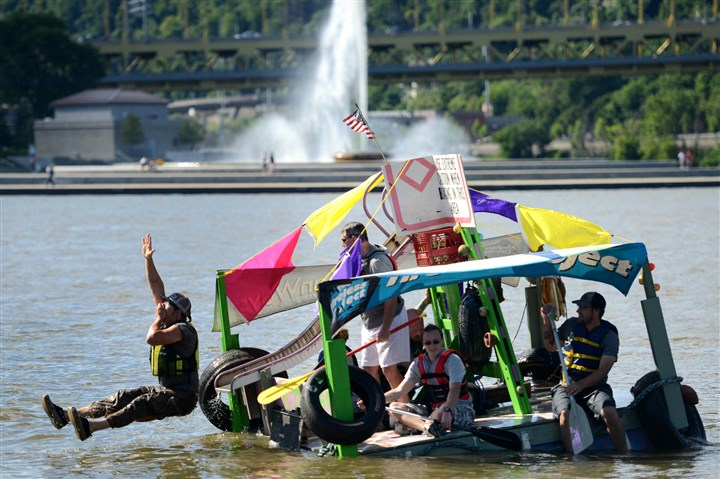20140701MWHfloatsLocal07-6 Evan Clark, of Polish Hill, slides into the water off a boat constructed by The Tireless Project during the Anything That Floats race this morning on the Allegheny and Ohio rivers as part of the Three Rivers Regatta, Downtown.