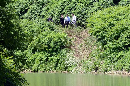 20140705lfClreekLocal01 Police officers investigate at a scene where a car became submerged in Chartiers Creek off of Creek Road in McKees Rocks on Saturday. A body was found in the vehicle.