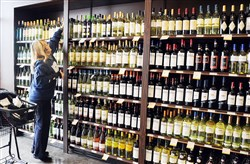 Linda Fitterer of McCandless reaches for a bottle of wine at a Fine Wine & Good Spirits Premium Collection store in the Village at Pine.