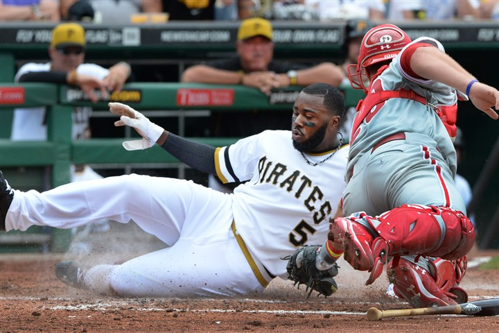 20140707pdPiratesSports04-4 Pittsburgh Pirates Josh Harrison slides safely past the tag of Phillies catcher Cameron Rupp at PNC Park.
