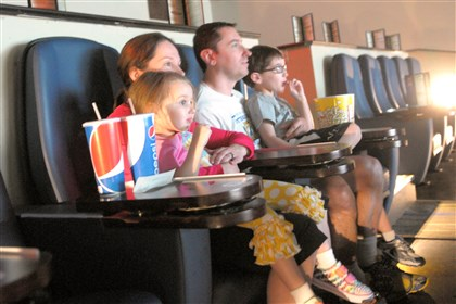 "20140628ttCineAllZones (2) Lisa and Vince Roskovensky of Moon, with their children, Hailey, 3, and Tyler, 6, watch ""Rio 2"" at the CineGrille, a dine-in movie theater, at Latitude 360 in North Fayette."