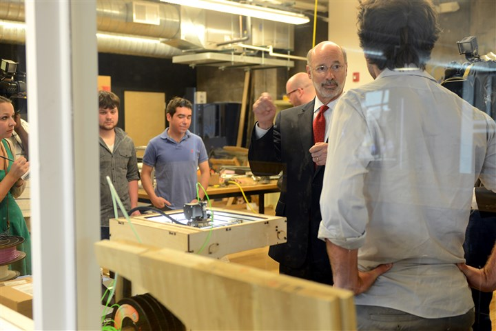 "2014070714RARwolf1-1 Tom Wolf talks with Alejandro Sklar, co-founder of PieceMaker Technologies about their 3-D printing technology. Mr. Wolf visited the Alphalab Gear facility, an incubator for companies in East Liberty as part of his ""Made in Pennsylvania"" manufacturing plan."