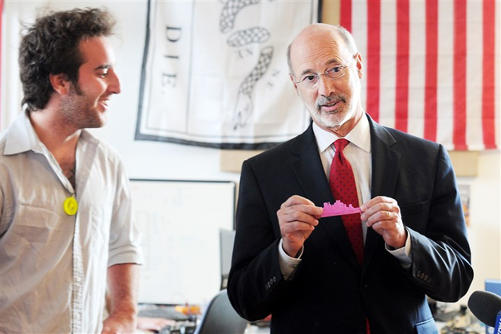 "20140707RARlocalwolf3-2 Tom Wolf holds up one of the plastic pieces given to him from Alejandro Sklar, co-founder of PieceMaker Technologies made by their 3-D printer. Mr. Wolf visited the Alphalab Gear facility, an incubator for companies in East Liberty as part of his ""Made in Pennsylvania"" manufacturing plan."
