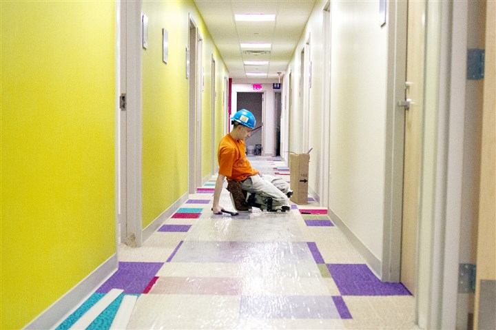ChildrensHospital-westextra2-1 Jason Ryan installs flooring Monday at Children's Hospital of Pittsburgh of UPMC in South Fayette. The outpatient, primary care facility is set to open in September.