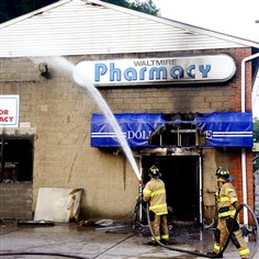 "20140708dsWaltmireFireLoc01-5 Firefighters return to the scene Tuesday morning to put out ""hot spots"" at Waltmire Pharmacy in Spring Garden."