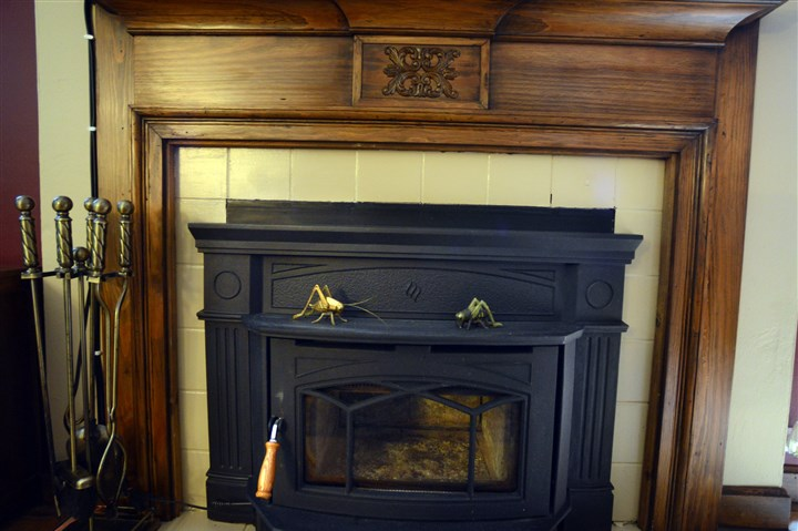 carved oak mantelpiece  Along the longer wall is a wood-burning fireplace with a ceramic tile surround and carved oak mantelpiece.