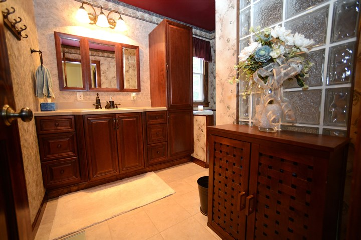 The main bathroom is L-shaped  The main bathroom is L-shaped with a tiled shower, a rainfall showerhead and glass block wall that lets in the light. There is a large cherry vanity with Corian counter top and a pantry-style cupboard at one end.