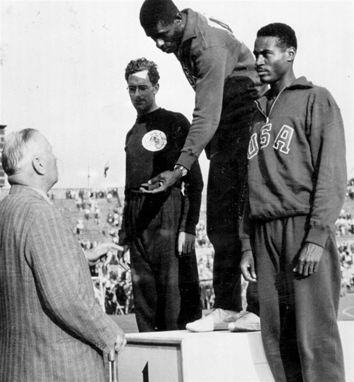 Herb Douglas, far right, waits at the podium  Herb Douglas, far right, waits at the podium to be awarded the bronze medal for his performance in the long jump.