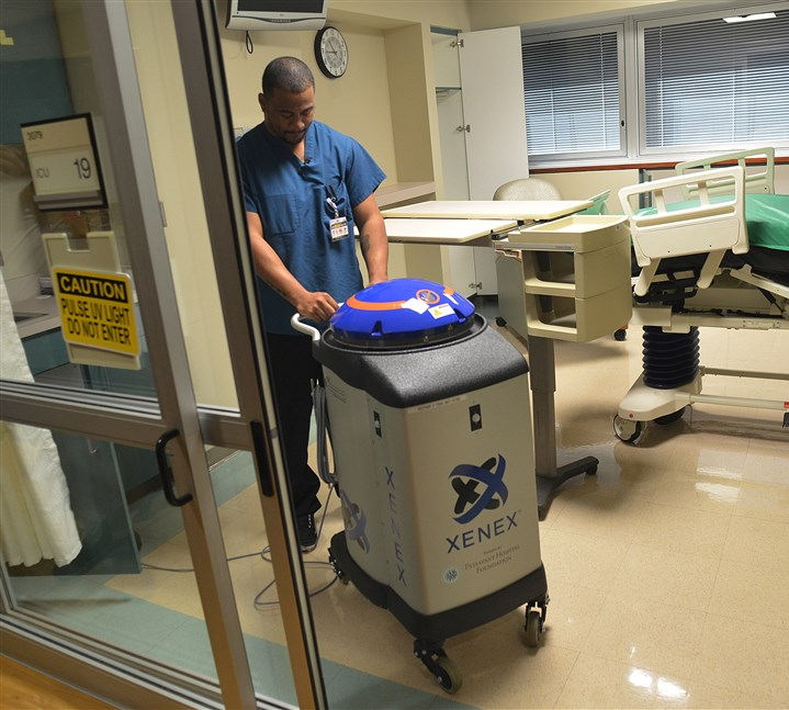 "Terrance Rhodes and Violet, a disinfecting robot Terrance Rhodes, from Environmental Services at UPMC Passavant, moves ""Violet,"" the disinfecting robot into position for a demonstration at UPMC Passasvant."
