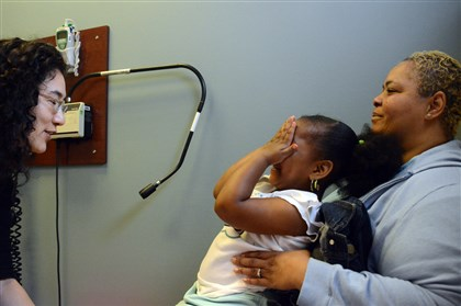 20140523lfHealthLocal02-1 Chloe Bibbens, 3, of the Hill District, covers her face while Erica Nakajima, a fourth-year medical student from the University of Pittsburgh, tries to talk to her during a visit with her mom, Darryl Hines, right, 47, at the Matilda Theiss Health Center in the Hill District.