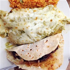 Mexican meal in Pilsen, Chicago. St Nuevo Leon, a taco and chicken enchiladas in corn tortillos topped with cheese and served with beans and rice. Pilsen is becoming a popular destination for tourists attracted to its dining, drinking and arts scene.