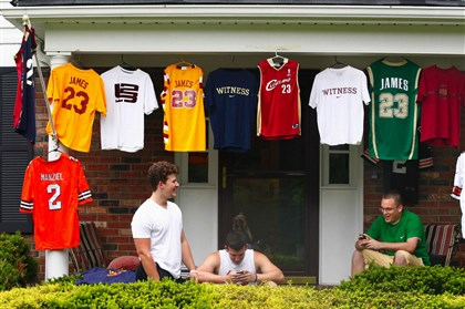 Cleveland fans Joe D'Amico, left, his brother Billy D'Amico, center, and their friend Josh Heckman, await the news of where LeBron James will play basketball next year under their LeBron James gear as they watch the fans and media gather in front of James' home Thursday in Bath Township, Ohio.