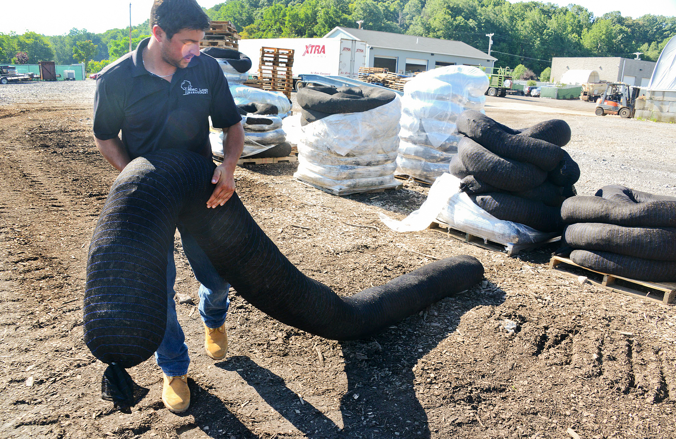 20140708dsDiamondsockBiz01 Christopher Platt, operations officer for MMC Land Management, carries a 24-inch pallet of Diamond Sock, a compost filter sock distributed by MKB Company.