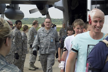 "20140712ssMockDisasterloc3-2 Lt. Jeff Shultz, right, boards a bus with other ""patients"" during a National Medical System exercise Saturday at the Pittsburgh Air Reserve Station."