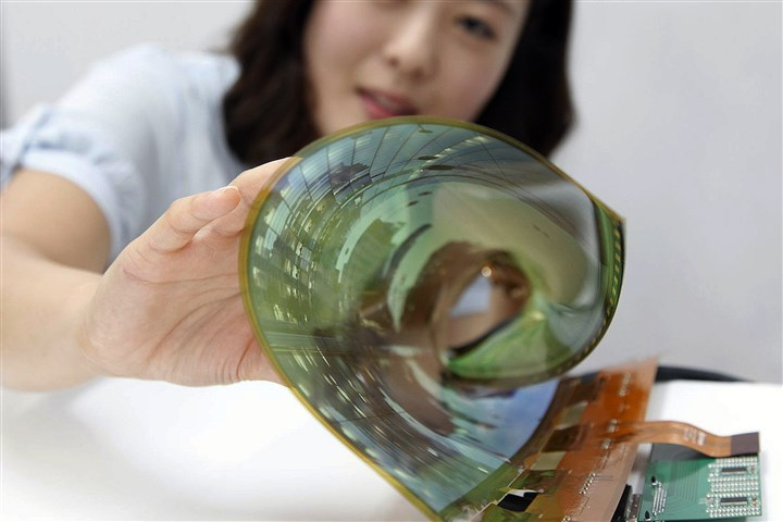 South Korea LG Display Flexible Display In this July 9, 2014 photo released by LG Display Co., an employee at the company demonstrates an 18-inch flexible display, in Seoul, South Korea. The South Korean display panel maker said Friday, July 11, 2014 it has developed the 18-inch flexible display that can be rolled into the shape of a thin cylinder, a step closer to making a large-size display for flexible TVs. (AP Photo/LG Display Co.)