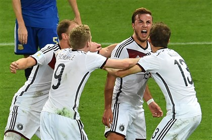 531616363 Germany's forward Mario Goetze celebrates after scoring with forward Thomas Mueller, forward Andre Schuerrle and defender Benedikt Hoewedes during extra-time in the final football match between Germany and Argentina for the FIFA World Cup at The Maracana Stadium in Rio de Janeiro.