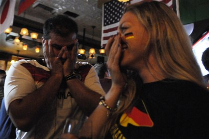 201407132CMWorldCupLocal001 Germany fans Dmitry Zaretsky of Shadyside and Roxanne Telegim of Greenfield react to their team's 1-0 loss to Argentina in the World Cup final match.