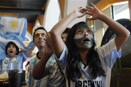 201407132CMWorldCupLocal002-1 Gabriela Ardiles, 9, with her father Pablo, of Wexford, foreground, and Jose Bravo of the North Hills watch the World Cup Final match between Argentina and Germany at Patron Mexican Grill in East Liberty on Sunday. Argentina lost to Germany 1-0.