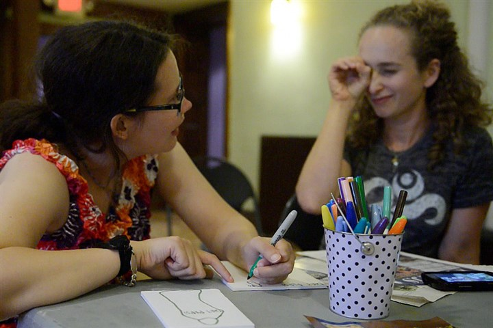 20140714rldCreativeCitizens06-5 Robyn McKee, 27, left, of Plum gets spelling help from Tirzah DeCaria, co-director of Creative Citizen Studios, during a session at the Union Project on Tuesday. Ms. DeCaria and Kirsten Ervin founded Creative Citizen to give people with developmental and intellectual disabilities an outlet for creativity and an opportunity to participate in community activities.