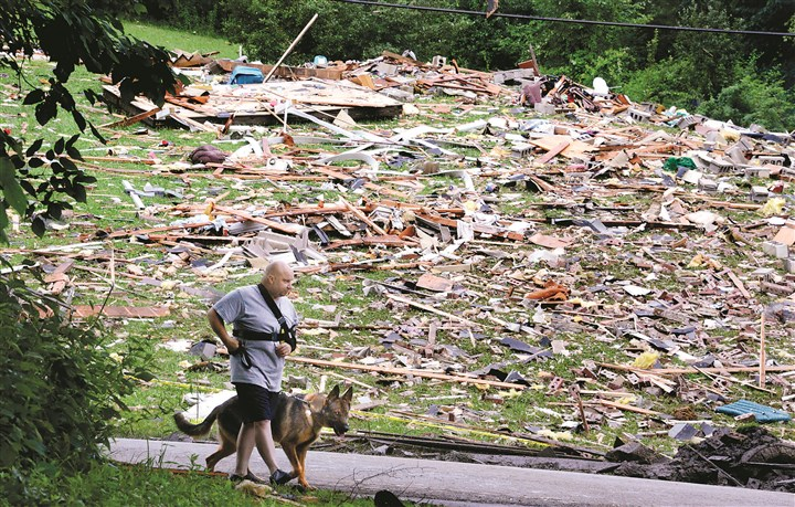 20140715dsExplosionLocal05 Carl DiRuscia and his dog Mia walk back to their house Tuesday after checking for damage following a propane explosion at a neighboring home that killed two people on ​​Louthan Road in South Beaver, Beaver County. The coroner idenified the victims as Ray ​​Trautvetter, 74, and his wife, Janet, 69.