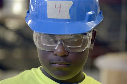 Holy Family students build desks 2 Marques Duncan wears his helmet and safety glasses as he works on a desk at the Keystone Mountain Lakes Regional Council of Carpenters and TechShop in Robinson.