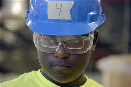 20140715dsHolyFamilyWestNorth02-1 Marques Duncan wears his helmet and safety glasses as he works on a desk at the Keystone Mountain Lakes Regional Council of Carpenters and TechShop in Robinson.