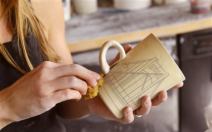 20140716lrceramicsmag07-6 Nicole Aquillano wipes away excess ink from a design etched into a ceramic mug.