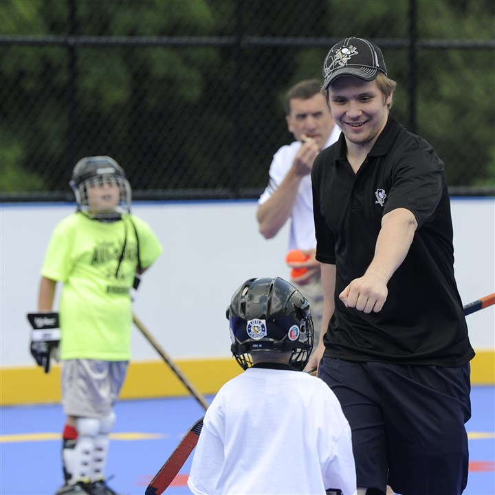 20140716rldPensProspects02-1 After scoring Penguins prospective player Anton Zlobin fist bumps a teammate during a scrimmage with members of the Brookline Youth Hockey League at Brookline Memorial Park on Wednesday.
