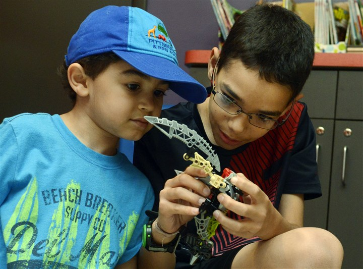 20140716bwLegoWest04-3 Brothers Jacob Carter, 5, and Zachary Carter, 10, of Imperial, work on their robot at the Lego Club Challenge at the Western Allegheny Community Library.