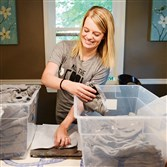 Kristin Estok, the Glenshaw co-owner of Go Shout Love, packs up orders at her dining room table. The company, an online startup, sells apparel and accessories to benefit families with sick children.
