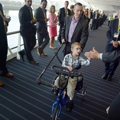 20140717MWHbikeBiz01 Six-year-old Domenic Angelucci, trailed by his father, Chris, high-fives members of the Pittsburgh Stock and Bond Club on Thursday while riding through the David L. Lawrence Convention Center on a specially designed bike that was donated by the club.