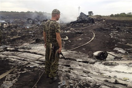 2014-07-17planecrash2 An armed pro-Russian separatist stands Thursday at a site of a Malaysia Airlines Boeing 777 plane crash in the settlement of Grabovo in the Donetsk region of Ukraine, killing all 298 people aboard, a Ukrainian interior ministry official said. Dozens of bodies were scattered around the smouldering wreckage of the passenger jet. An emergency services rescue worker said at least 100 bodies had so far been found at the scene, near the village of Grabovo, and that debris from the wreckage was spread across an area up to about nine miles in diameter.