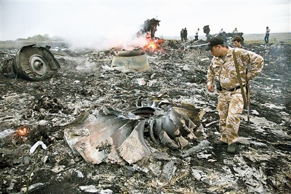 9r500ngr-26 People walk among the debris at the crash site of a Malayasian passenger plane near the village of Grabovo, Ukraine on Thursday. Officials say the plane carrying 298 people was shot down.