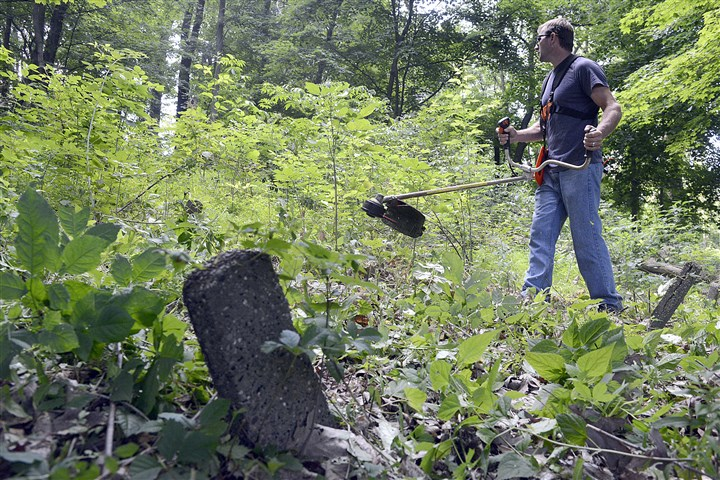 Dixmont cleanup 2 Donald Yahnert clears his clogged trimmer as he cuts underbrush at the overgrown cemetery at the former Dixmont State Hospital in Kilbuck today.