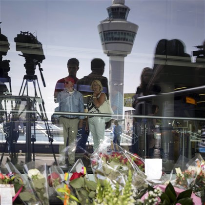 Netherlands Ukraine Plane The Schiphol traffic tower is reflected in a window behind flowers placed outside Schiphol airport in Amsterdam today. The attack on a Malaysian jetliner Thursday afternoon killed 298 people from nearly a dozen nations, more than half being Dutch and including one American.