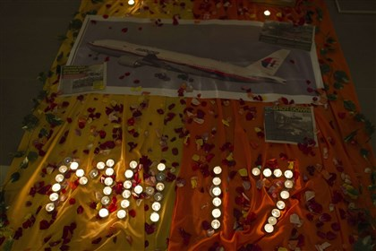 "MH 17 memorial A memorial with candles that read ""MH17"" is seen with tissue, flower petals and a photograph of a Malaysia Airlines plane as unseen churchgoers pray for the victims of flight MH17 from Amsterdam to Kuala Lumpu."