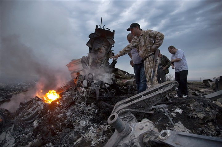 9r500nky People inspect the crash site of a passenger plane Thursday near the village of Grabovo, Ukraine. Ukraine said a passenger plane carrying 295 people was shot down Thursday as it flew over the country. Both theUkranian government and the pro-Russia separatists fighting in the region denied any responsibility for downing the plane.