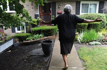 20140719SSgardenersMag6-5  Carolyn Collier gestures to her Penn Hills home surrounded with plants. She said she keeps a journal to remember what she planted and where.