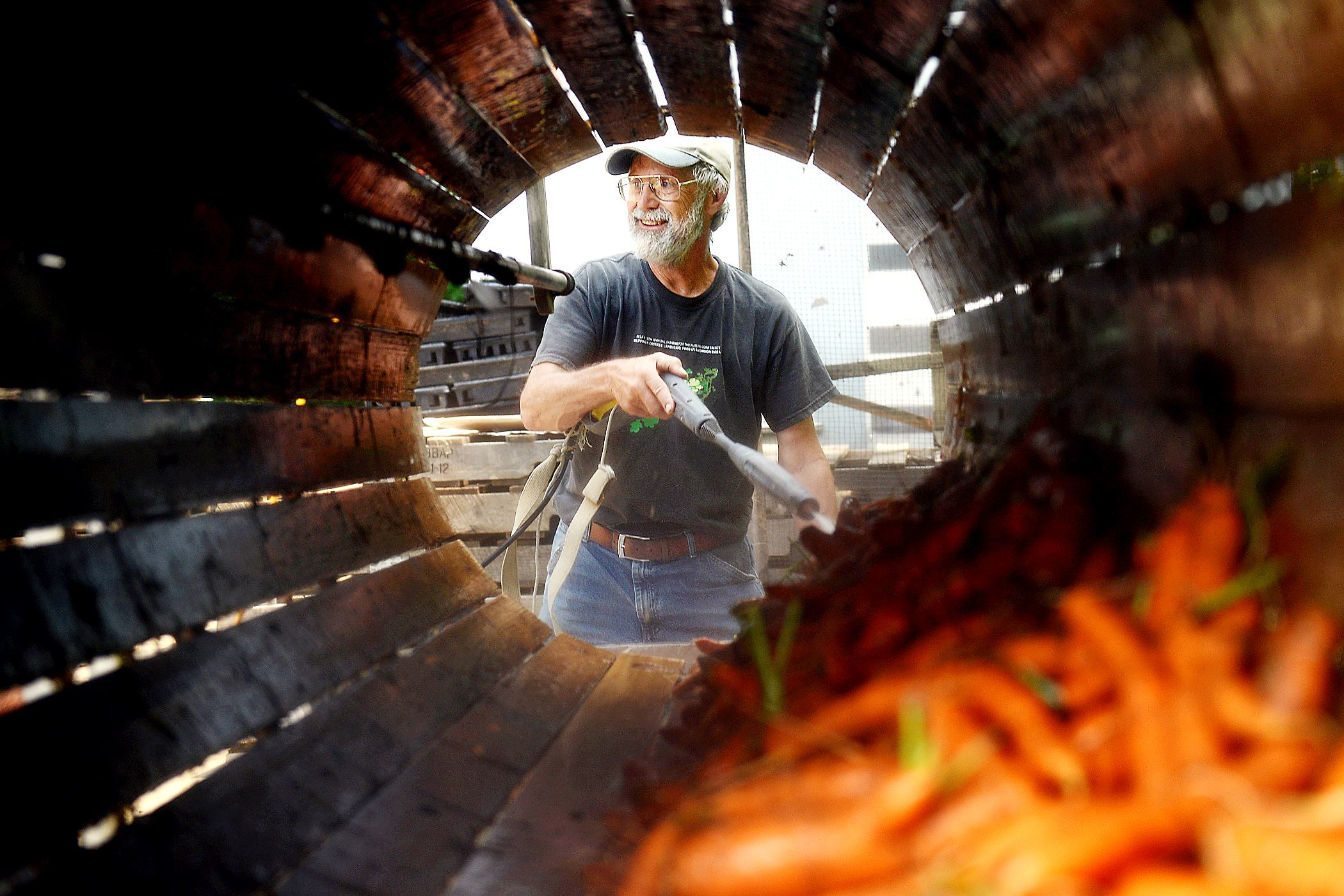 07212014jrOrganicLocal1 Don Kretschmann, owner of Kretschmann Family Organic Farm, cleans carrots July 21 at his farm in Rochester.