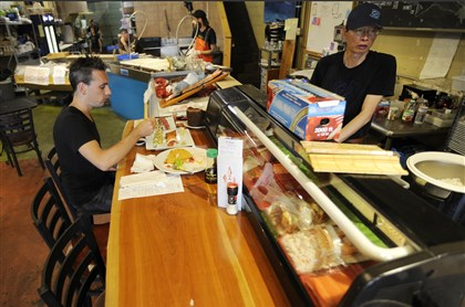 20140724CMTableMag004-3 Christopher Farley of Greensboro, N.C., enjoys sushi served by Jake Qing at Penn Avenue Fish Company.