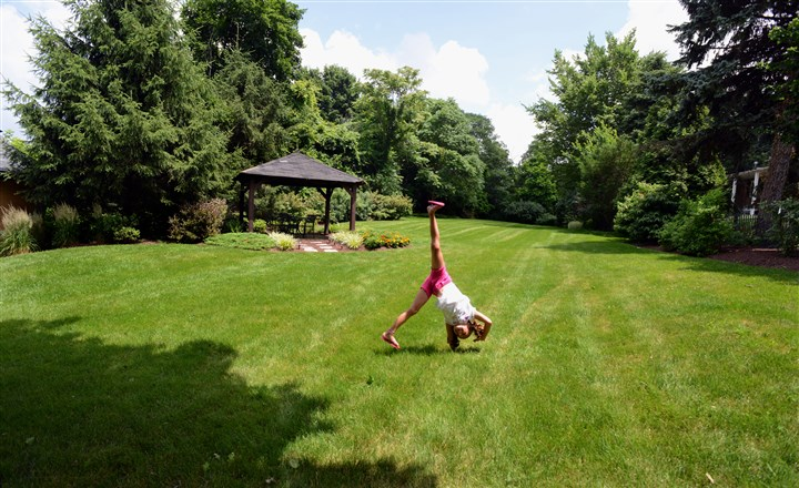 2014630RARmagbrentwood7  Elizabeth Seiffert does cartwheels in the backyard of her grandparents, Bill and June Sheppard. This area was once covered in asphalt for parking.