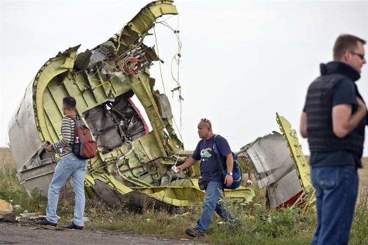 9ra00lek-12 Malaysian air crash investigators walk by wreckage at the crash site of Malaysia Airlines Flight 17 near the village of Hrabove, eastern Ukraine Tuesday. A team of Malaysian investigators visited the site along with members of the OSCE mission in Ukraine for the first time since Thursday's air crash.