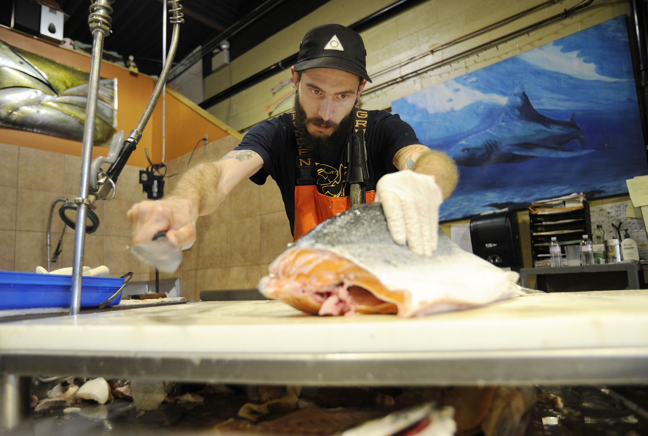 20140724CMTableMag003-2 Kyle Houghtelin of Braddock cleans a salmon at Penn Avenue Fish Company.