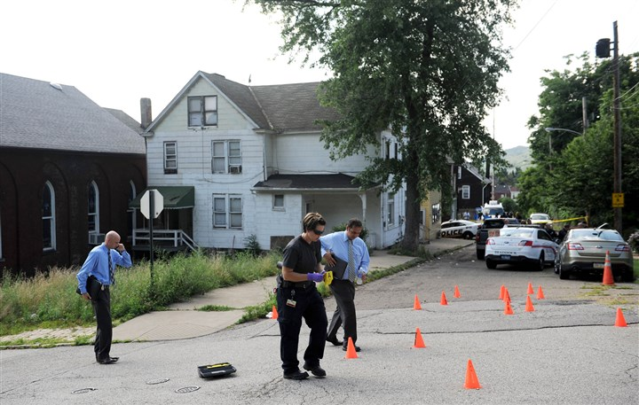 20140723MWHshootingLocal01-7 Investigators mark shell casings at the intersection of Jones Avenue and Hickory Street in North Braddock at the scene where four people were shot by multiple gunman.