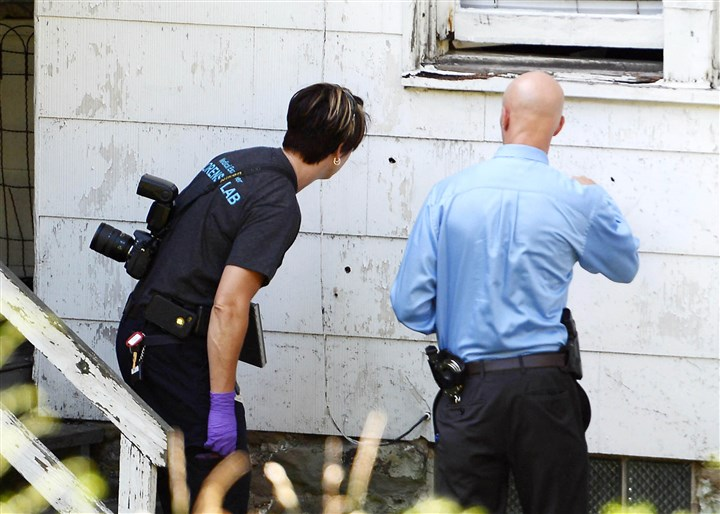 20140723MWHshootingLocal06-12 Investigators look at bullet holes on a house at Jones Avenue and Hickory Street in North Braddock.