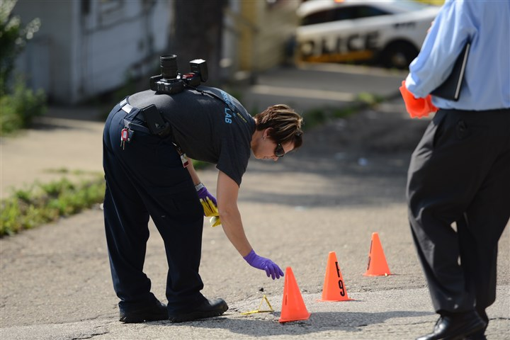 20140723_shootingscene Forensic investigators mark shell casings at the scene of a shooting on Hickory Street at Jones Avenue in North Braddock.