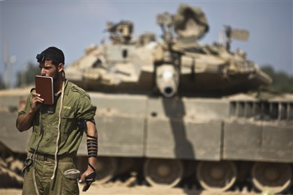 Tel Aviv 0724 An Israeli soldier prays in front of a tank at a military staging area near the border with the Gaza Strip today.