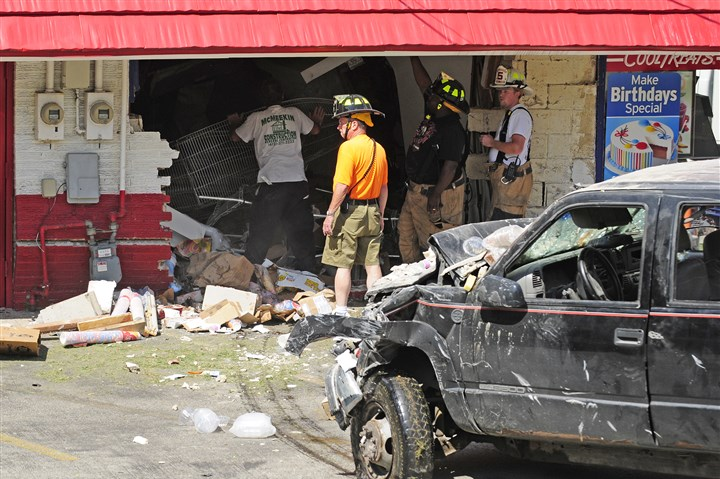 20140724CMDairyQueenLocal002-1 First responders clear the site of an accident where a truck drove through the wall of a Dairy Queen on Verona Road in Penn Hills.